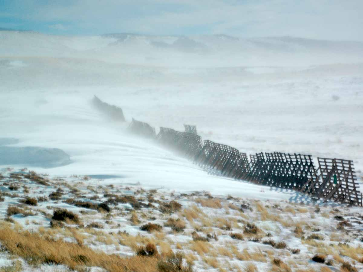 Wyoming snow fence directing snow away from a road.