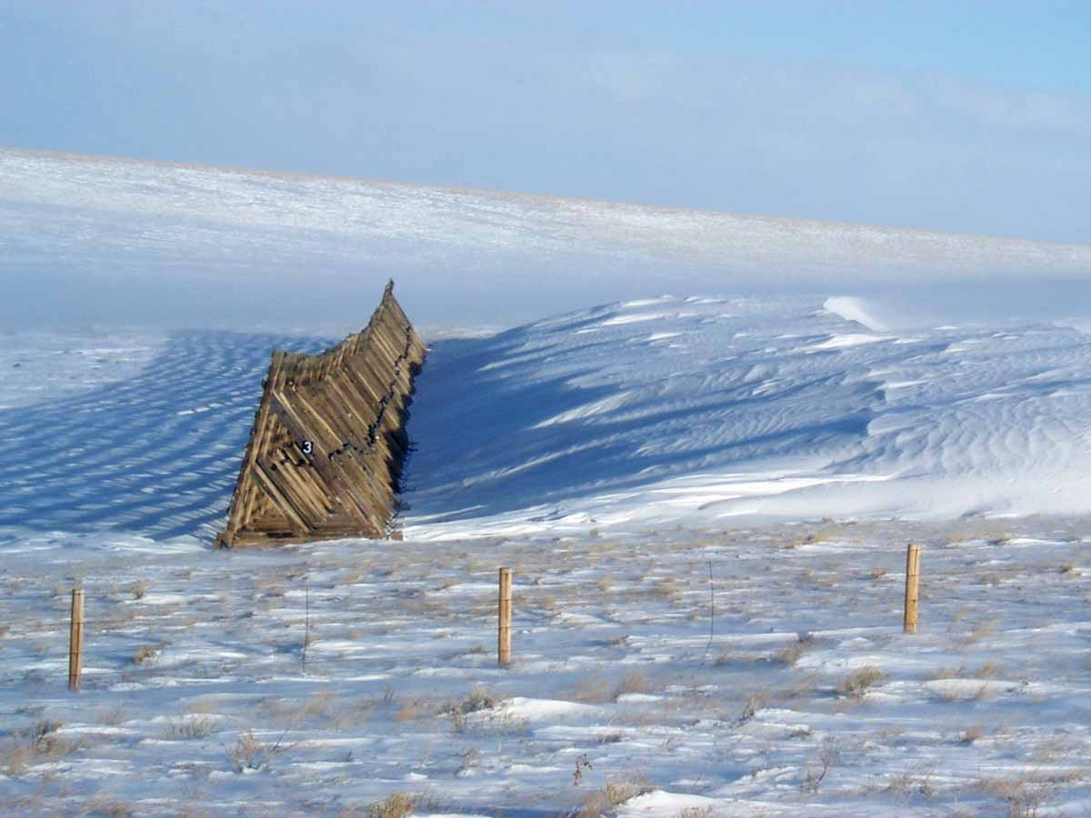 A snow fence in Wyoming directing snow away from the highway.