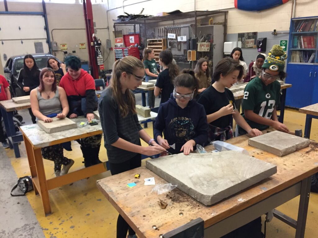 Several girls work on a cement tile.