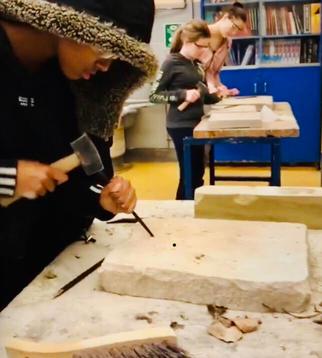 A girl uses a mallet and chisel.
