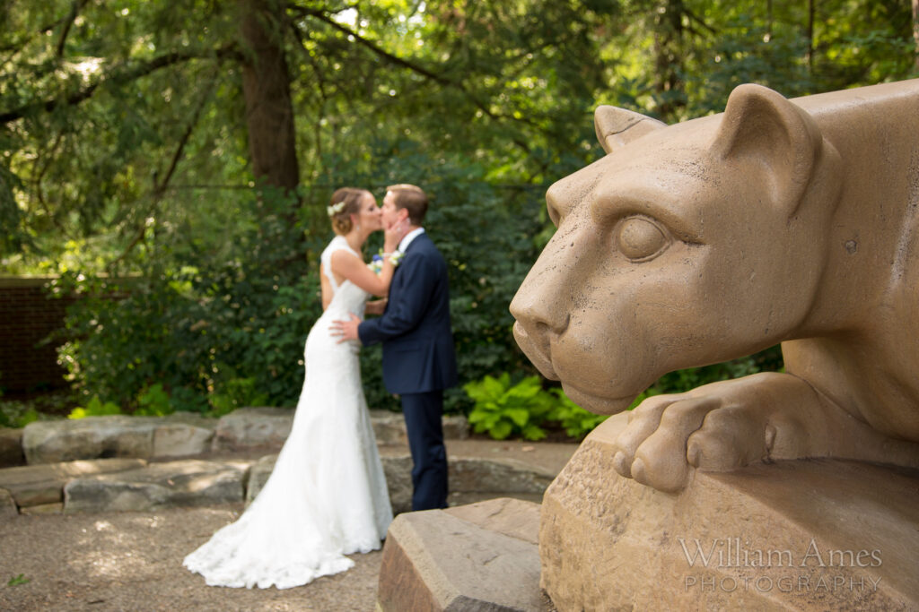 A couple kisses behind the nittany lion during their wedding
