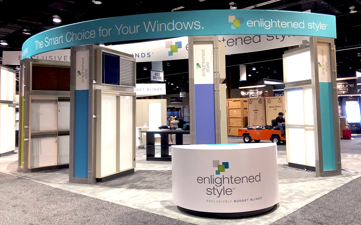 Curved face info desk and curved fabric wrapped header above four custom built product displays for Budget Blinds' trade show booth exhibit
