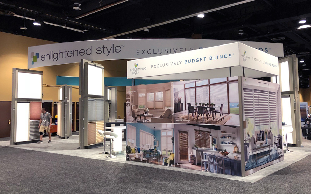 Enlightened Style Trade Show Booth with view of custom blinds display, backlit rental bistro table, custom built storage area wrapped with graphics and fabric wrapped headers