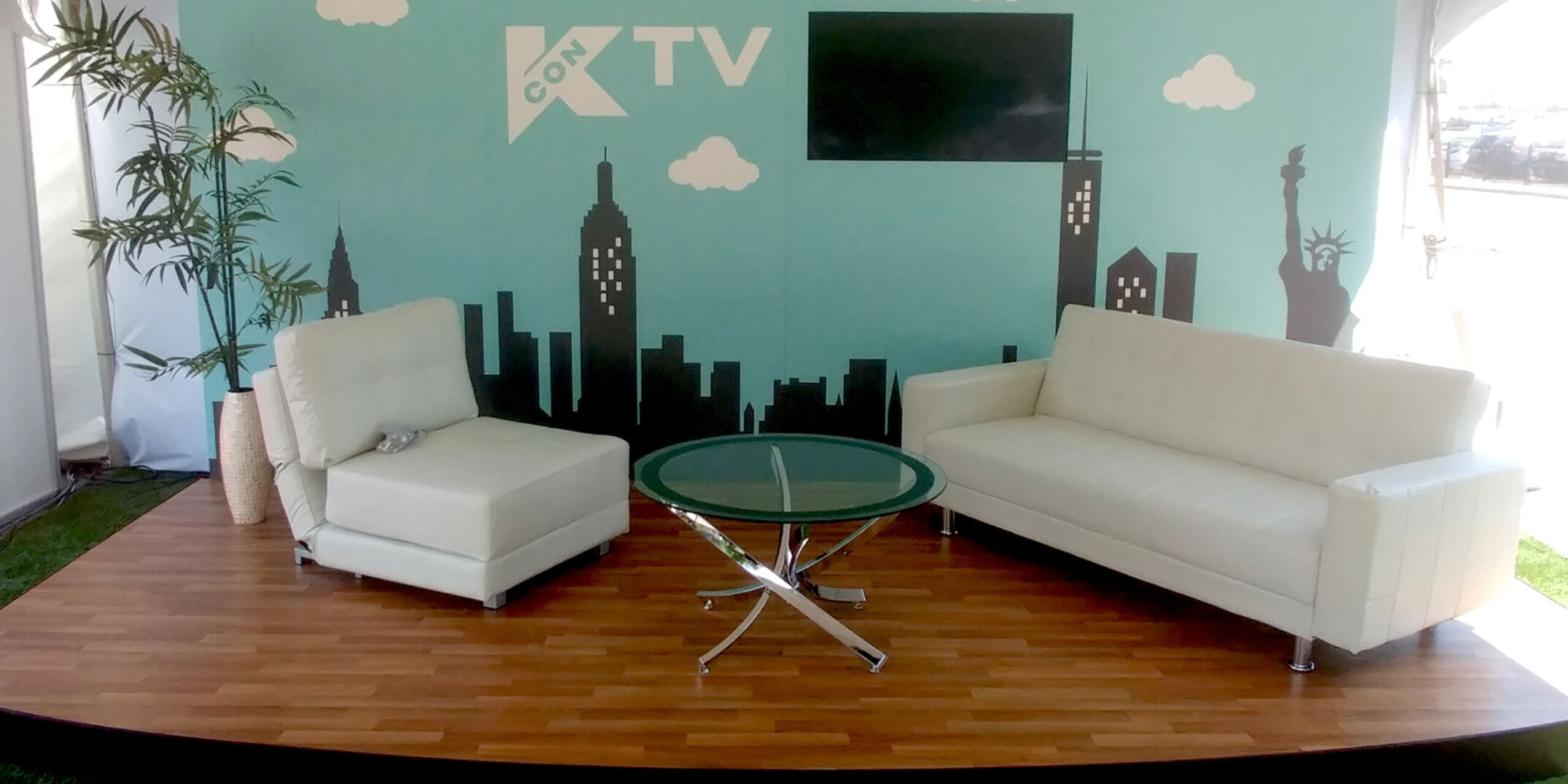 demo backdrop. TV set stage for Kcon with graphic wall, wood flooring, monitor and modern furniture for TV interviews