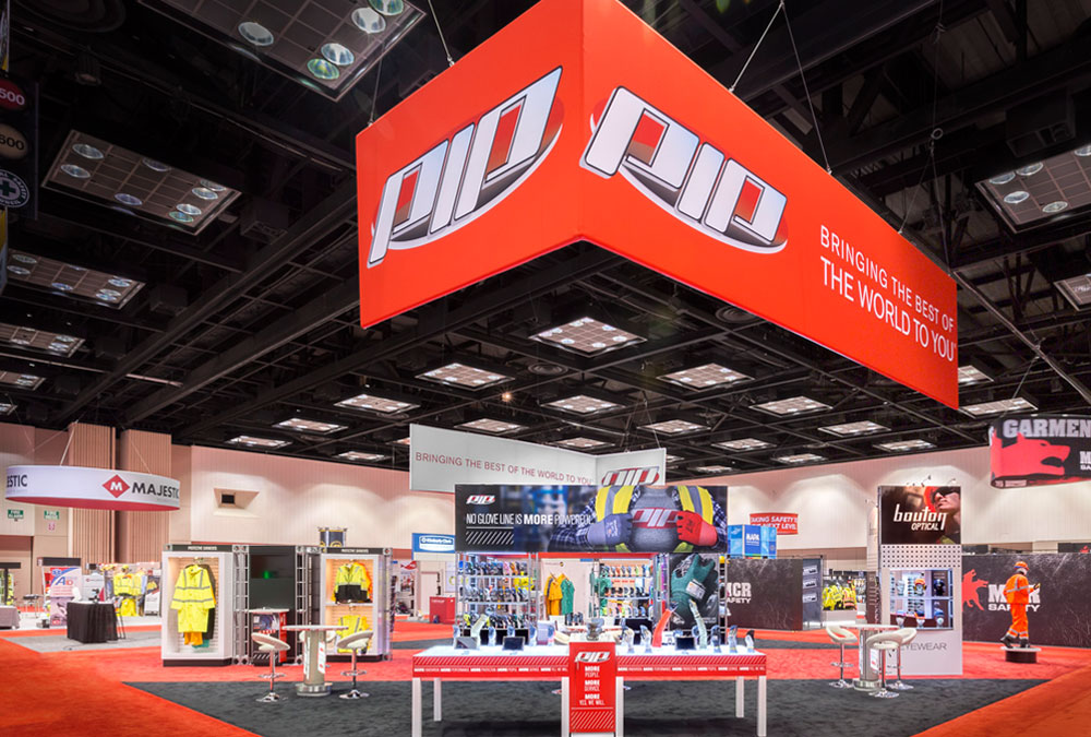 PIP trade show booth red hanging header, custom product display pods, tables and graphic wall storage area
