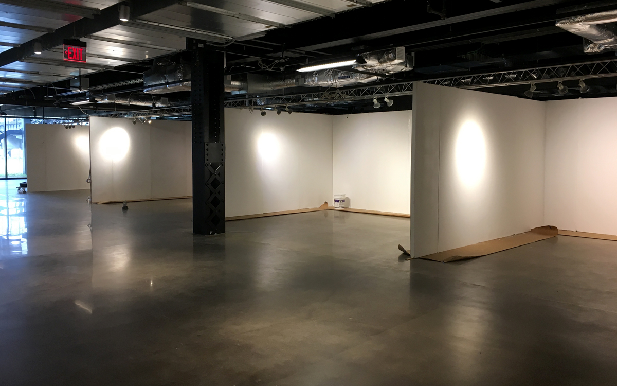 Set-up shot of gallery wall rentals with truss lighting in urban setting