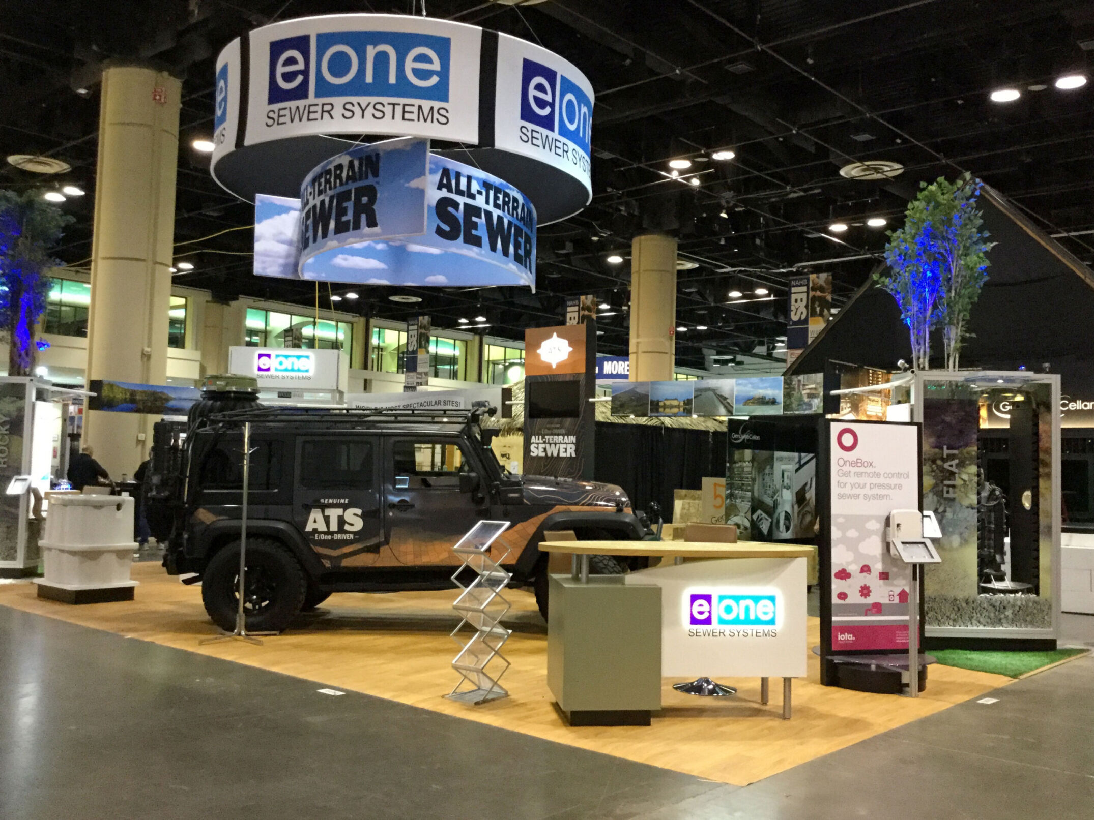 Trade show booth with graphic wrapped jeep, info desk and custom displaysor EOne