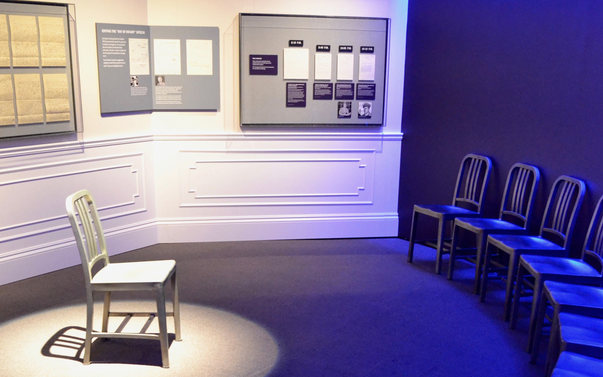Museum exhibit with a chair under spotlight surrounded by chairs lighted in blue. Walls have mounted display cases and graphic panels