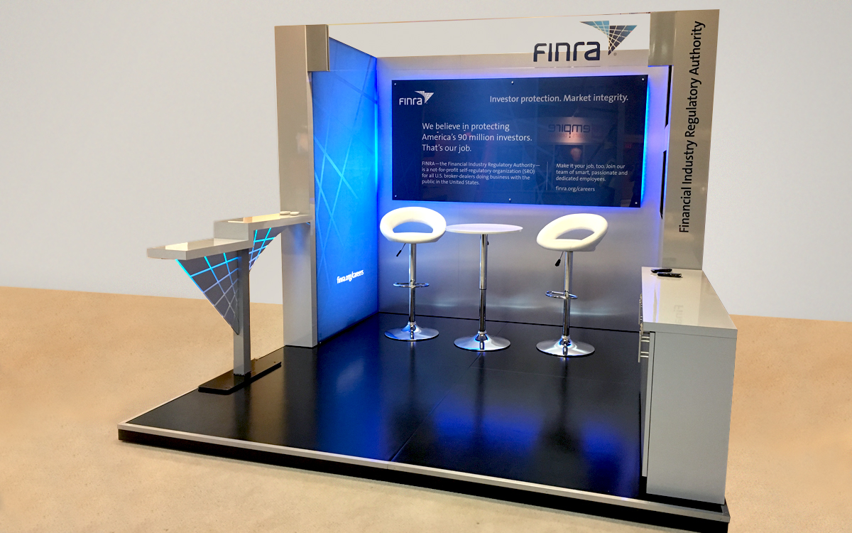 10' x 10' trade show booth for FINRA with two monitors, blue LED lighting, raised base, storage cabinets, custom header and lighted counter elements