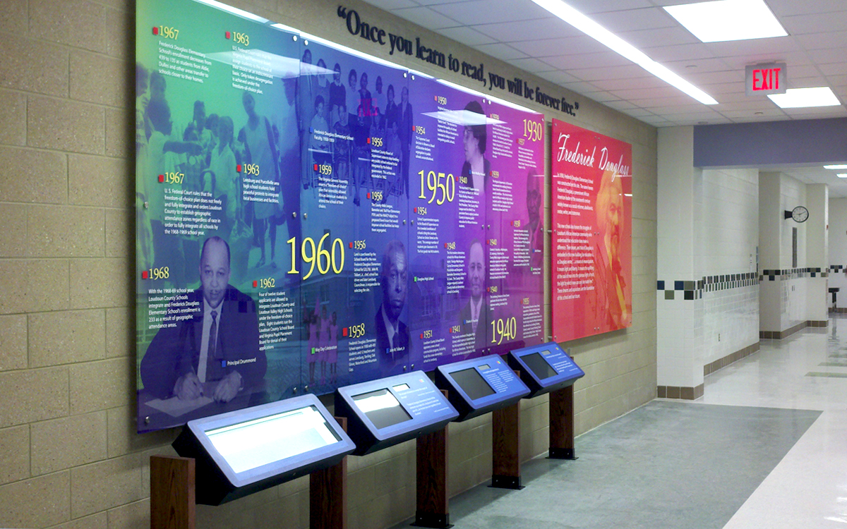 Graphic wall panels with custom kiosks in a school hall