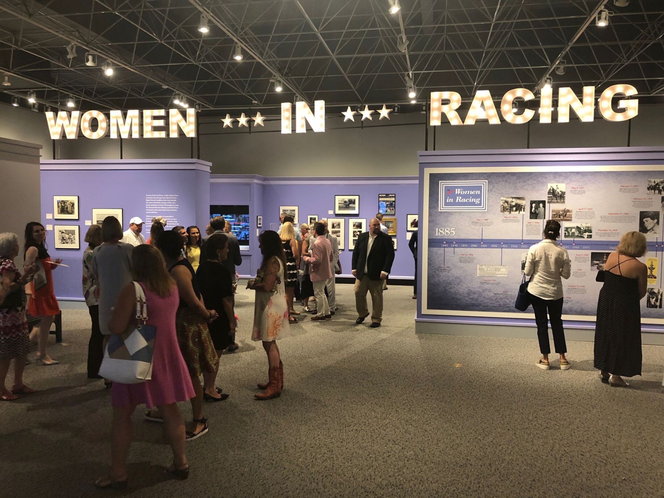 People at museum exhibit for Women In Racing Exhibit at the National Racing Museum and Hall of Fame