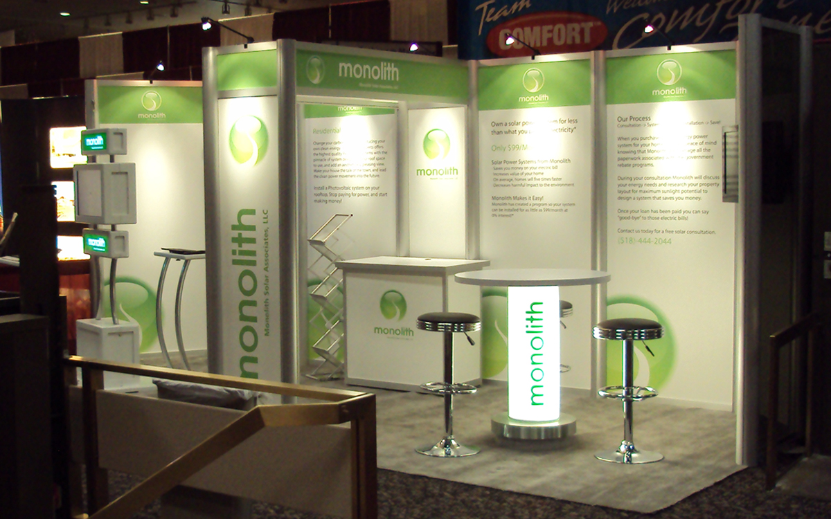 10' x 20' trade show booth for Monolith Solar with custom kiosk and backlit bistro table