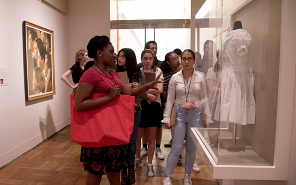 Tour group with custom built display case holding a dress in the Norman Rockwell Museum