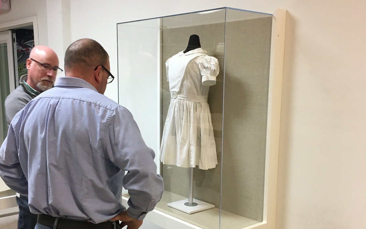 Norman Rockwell museum case display housing a dress. Two people view the case.