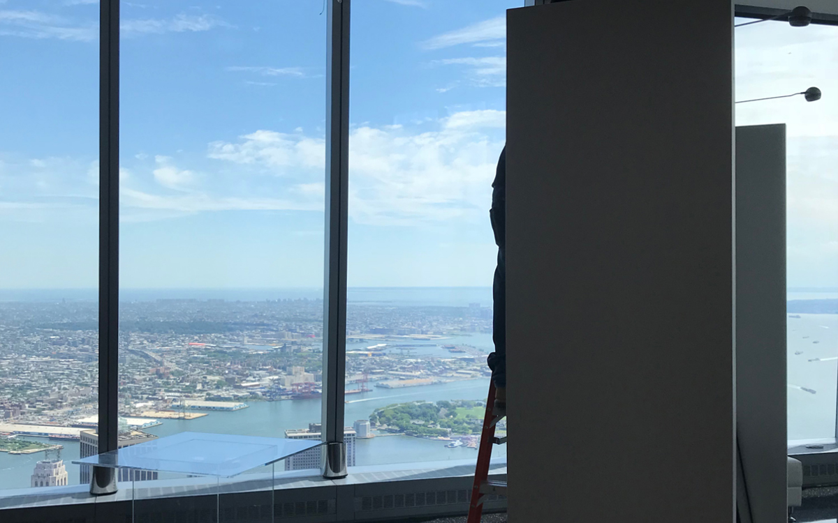Worker installing lights on rental gallery walls by a window viewing New York City