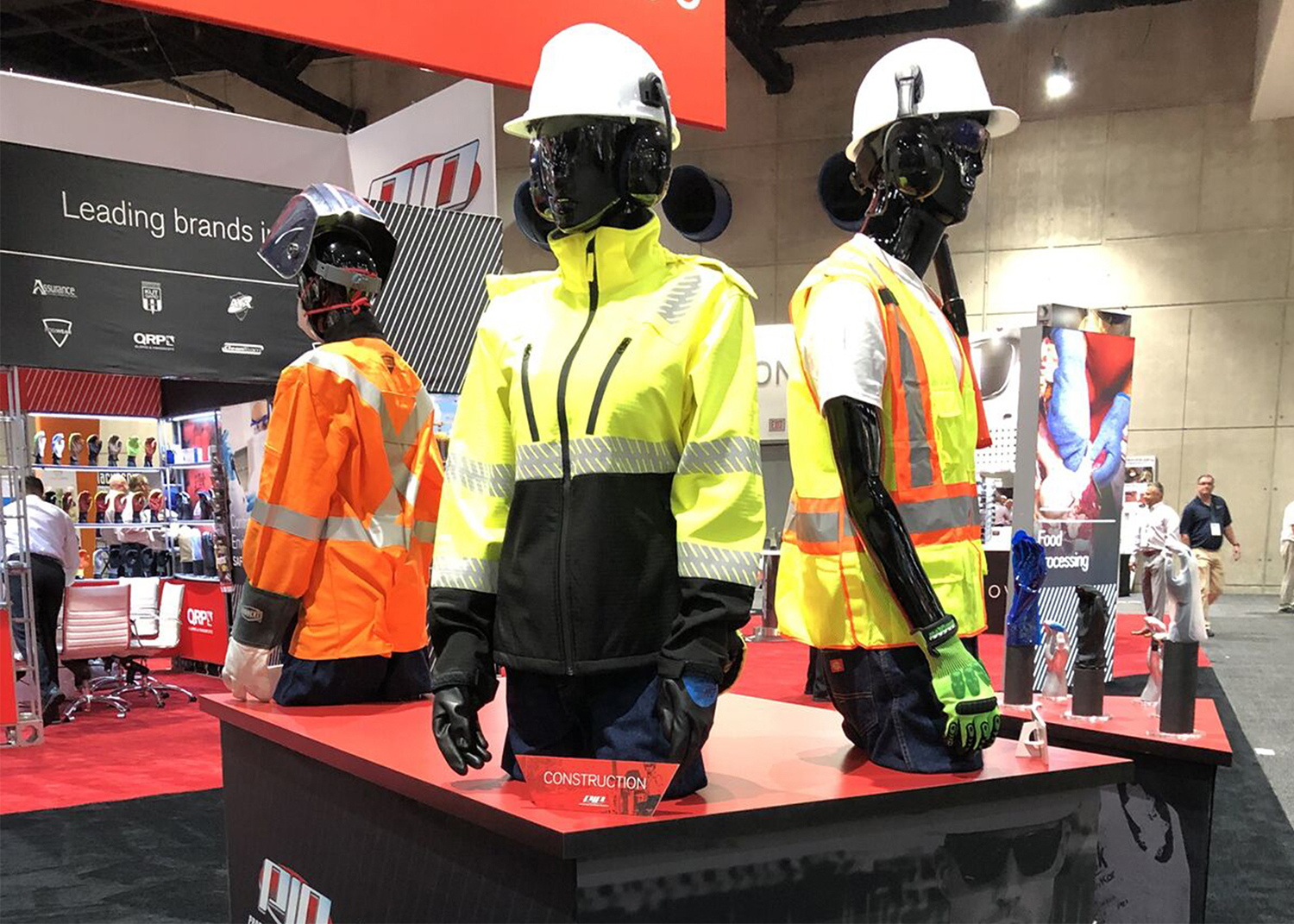 Trade show exhibit booth with PIP construction worker mannequins mounted to red and black angled tables