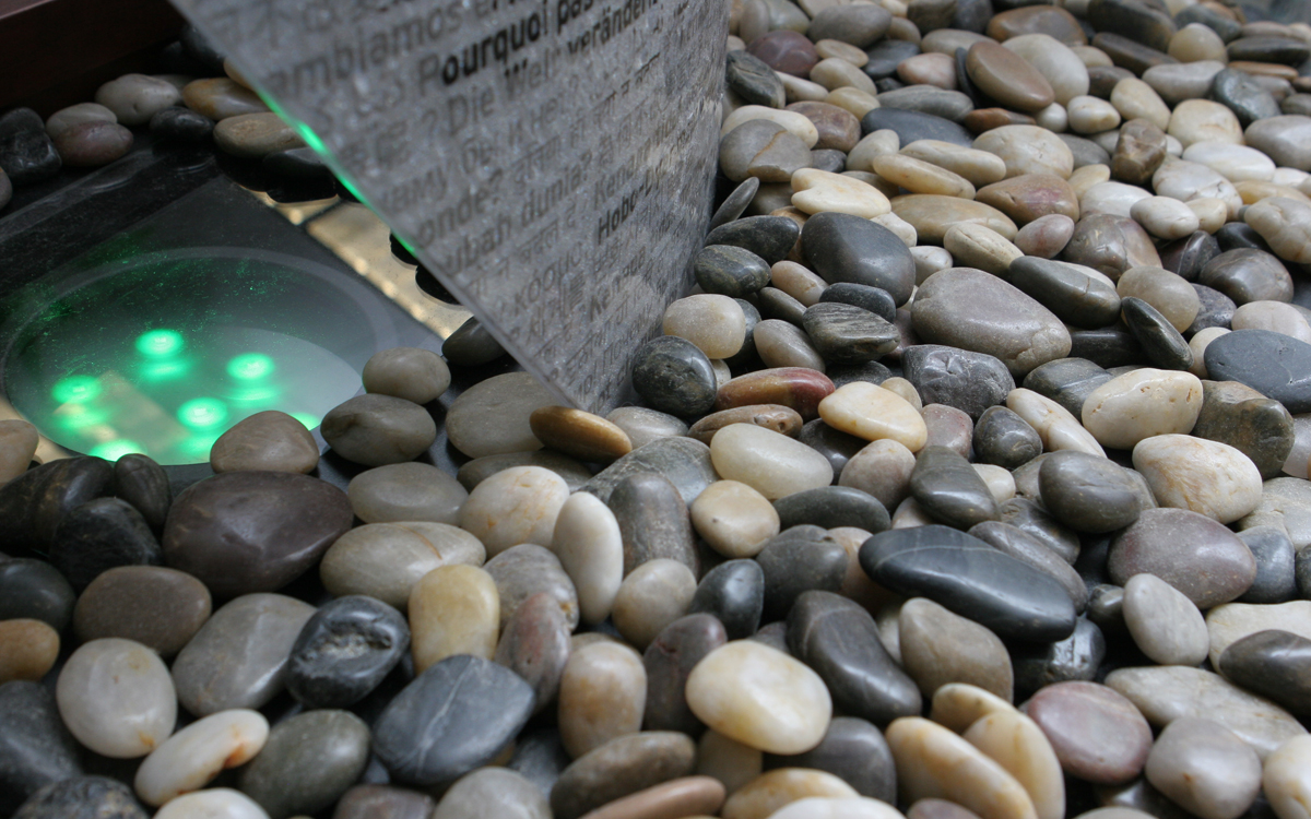 River rock and teal lights closeup for the sails room divider display at RPI Folsom Library
