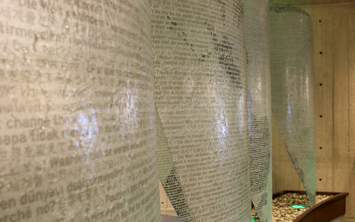 Custom privacy panels in the shape of sails with the world map printed using multiple languages of text for shading. Teal up-lighting comes from a bed of river rock in the Folsom Library at RPI
