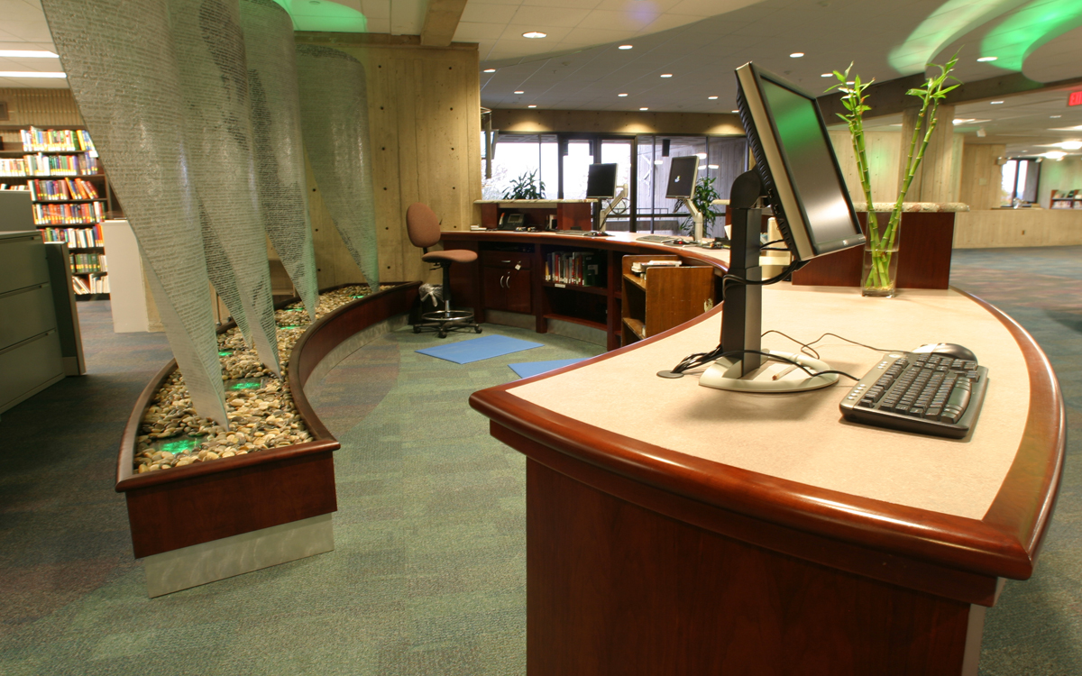 Custom built curved desk and teal lighted art accent with river stones