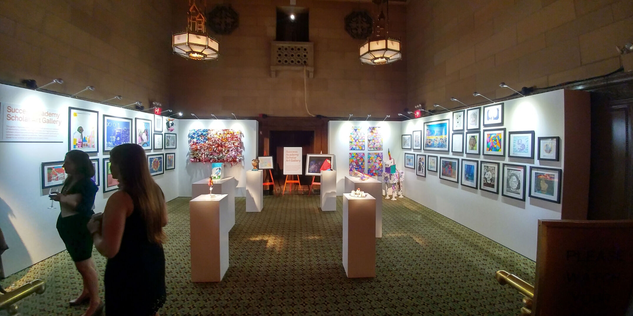Rental gallery walls and pedestals with stem lights with hanging artwork and 3D artwork on display at art exhibit