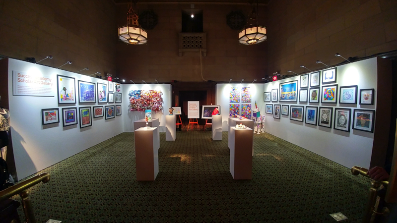 Rental gallery walls and pedestals with stem lights with hanging artwork and 3D artwork on display