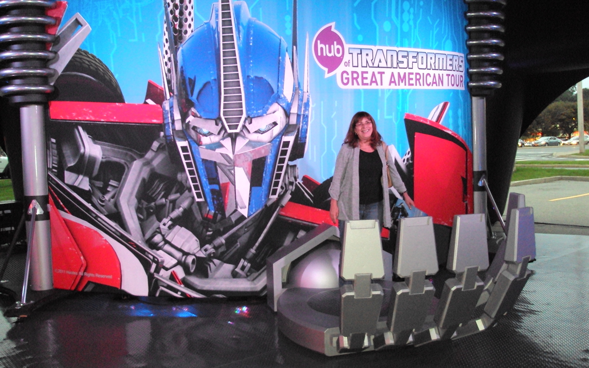 Custom interactive display with woman standing in Optimus Prime's metal hand for a photo op at the Transformers Great American Tour
