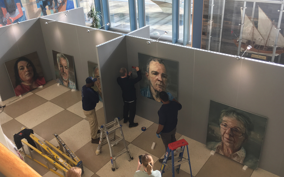 Workers hanging art on Gallery Rental Walls in gray for portrait art exhibit in the United Nations building in NYC