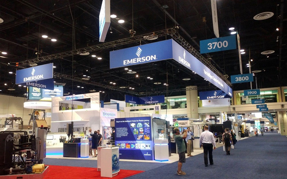 Emerson trade show booth with custom blue LED lighted display cases and custom kiosks