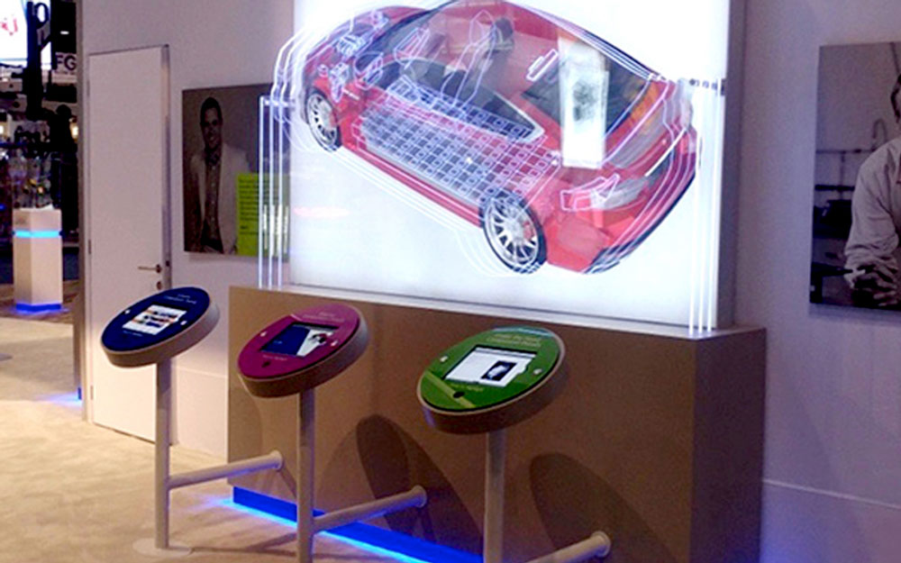 Empire exhibits custom interactive kiosk with LED lit car graphic. Different areas of the car light up with glowing outline with use of the monitor kiosks