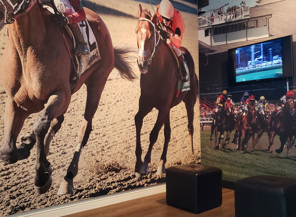 interactive kiosk at horse racing museum ottoman seating and monitor