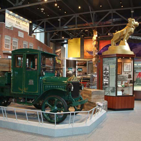 Custom built storefront, display cases, turntable with statue and rails around museum displays for America on Wheels