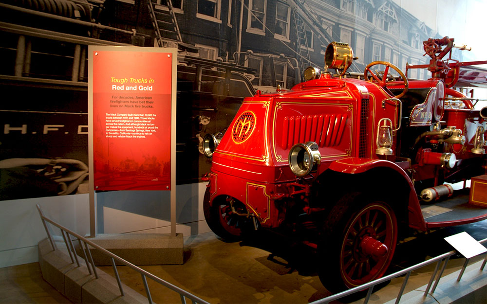 Fire truck museum exhibit with signage panel and reading rails