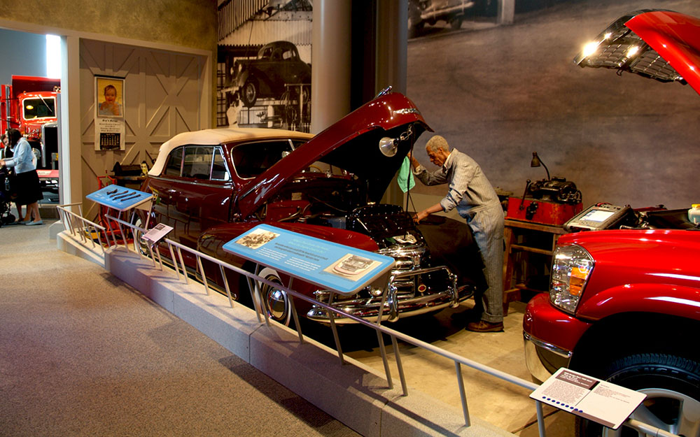 Permanent installation of mannequin mechanic working on hotrod cars exhibit for America on Wheels