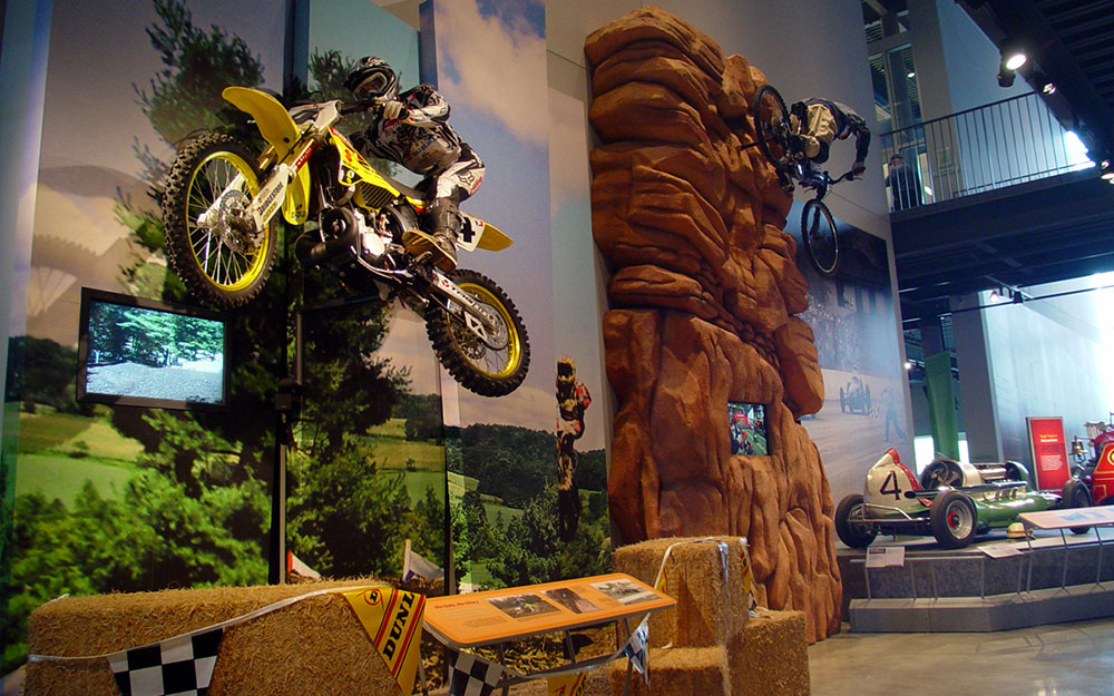 Custom rock wall with mounted bike and mannequin, wall graphics and monitor for America on Wheels museum exhibit