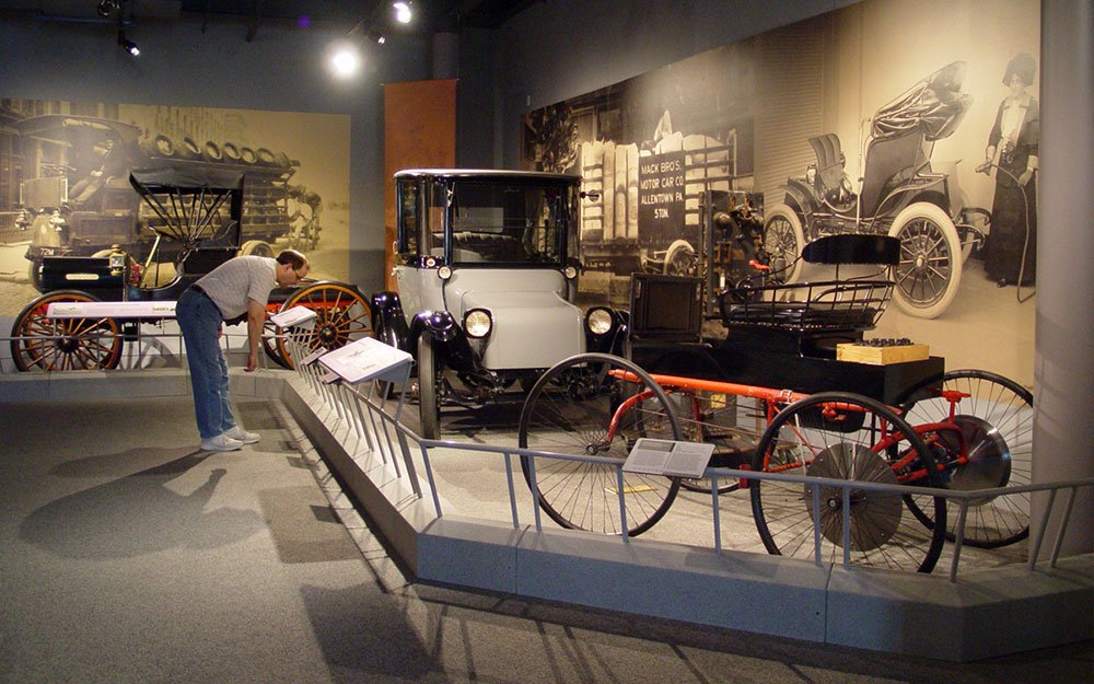 Man reading graphic reading rail at the America on Wheels Museum exhibit