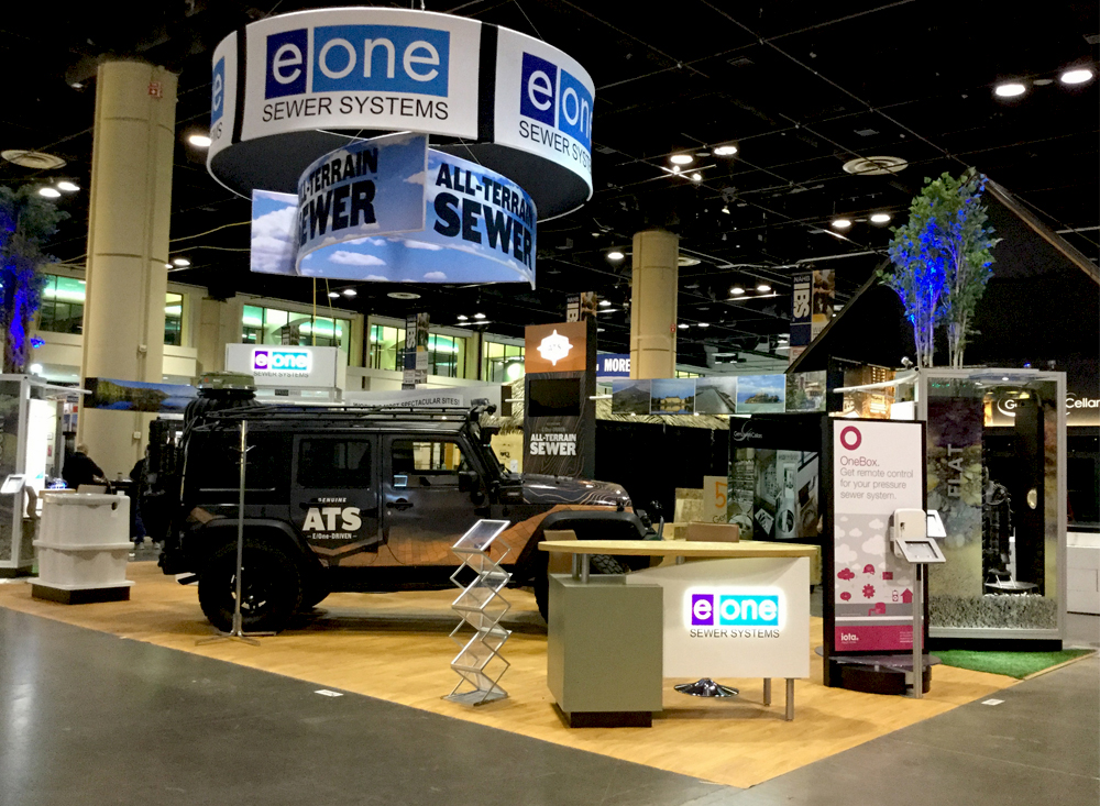 Trade show booth for Environment One with Jeep, plants and hanging signs