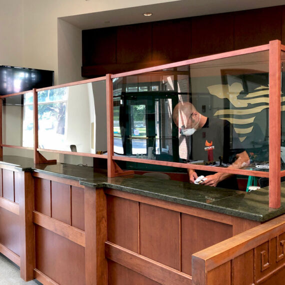 Acrylic protective shild framed in cherry wood and mounted to green granite counter in a row
