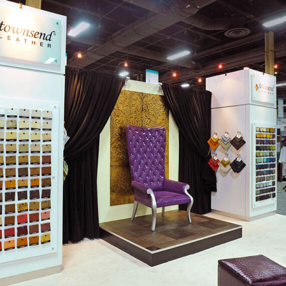 Trade show exhibit booth with purple chair display, stem lighting and sample racks for Townsend Leather