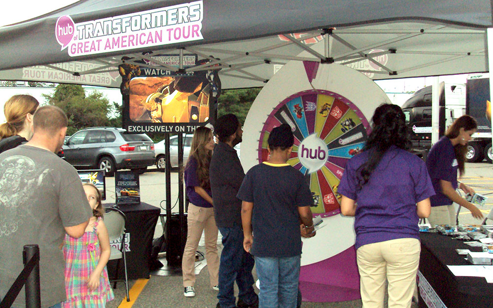 People gathered to spin a custom fabricated wheel for prizes at the Transformers Great American Tour