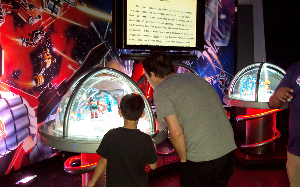Two people viewing collectibles inside custom dome display cases for Transformers Great American Tour