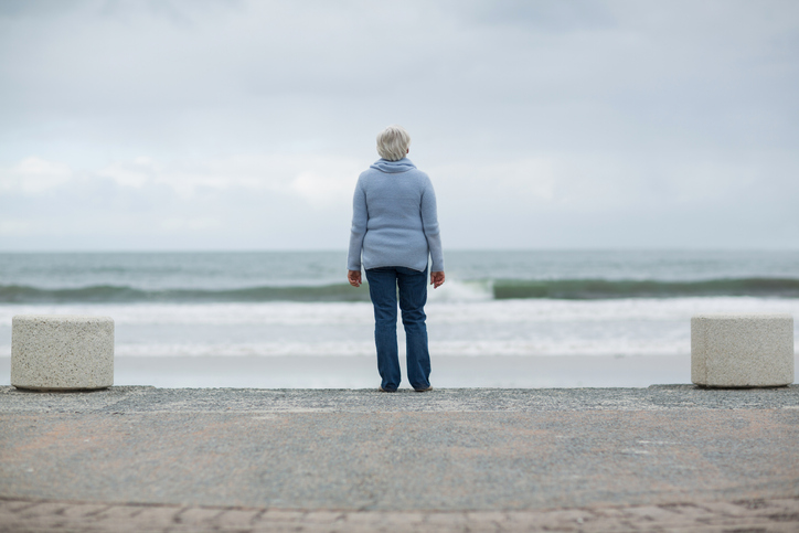 Rear view of senior woman standing on the beach