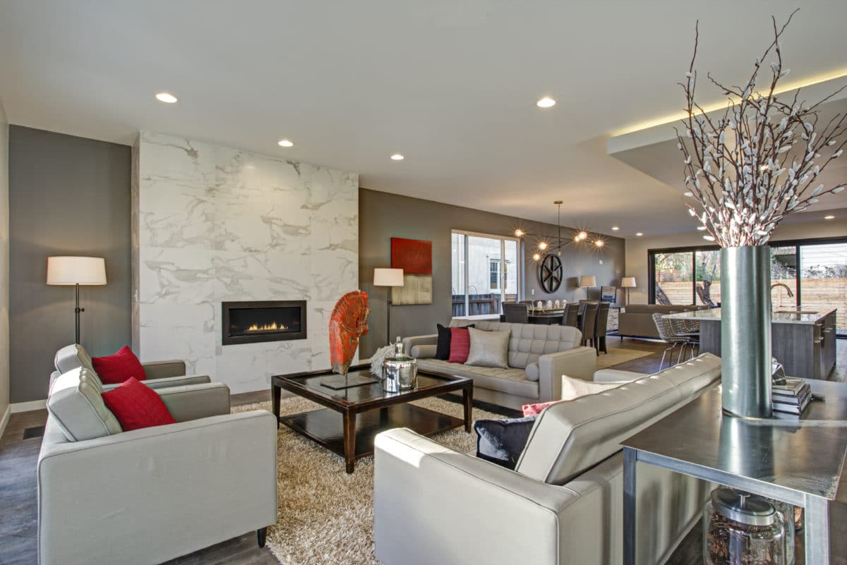 Large luxury home interior with open floor plan features modern kitchen, spacious dining area and gray and white living room with gorgeous fireplace.
