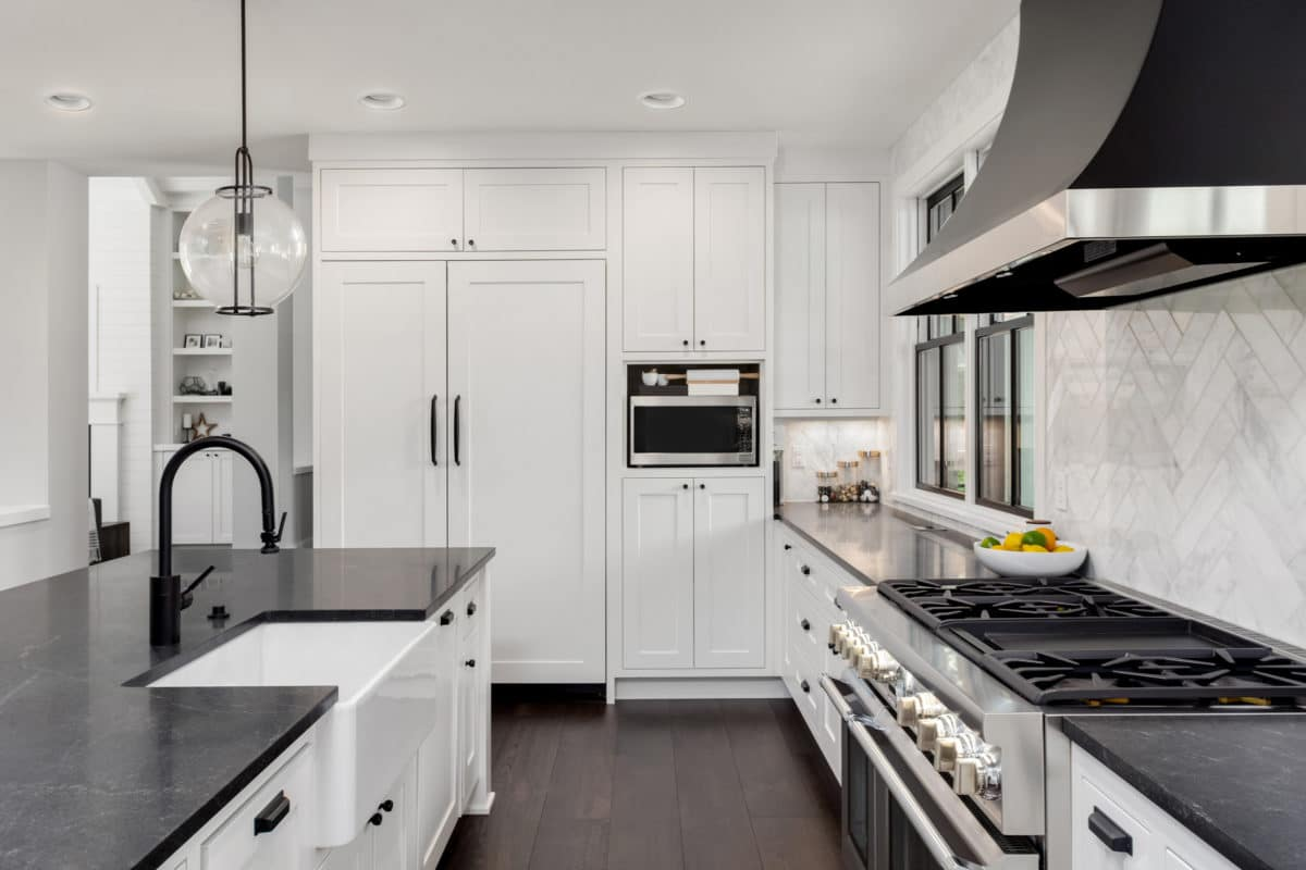 Beautiful Kitchen With Farmhouse Sink, Dark Soapstone Counters, Kitchen Island, and Refrigerator