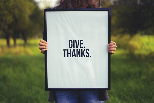 "Photo by Simon Maage/Unsplash Person holding sign ""give thanks."" You can begin a gratitude practice when life is hard."