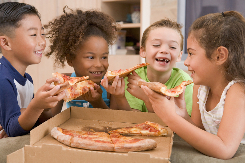 4 young children eating pizza together