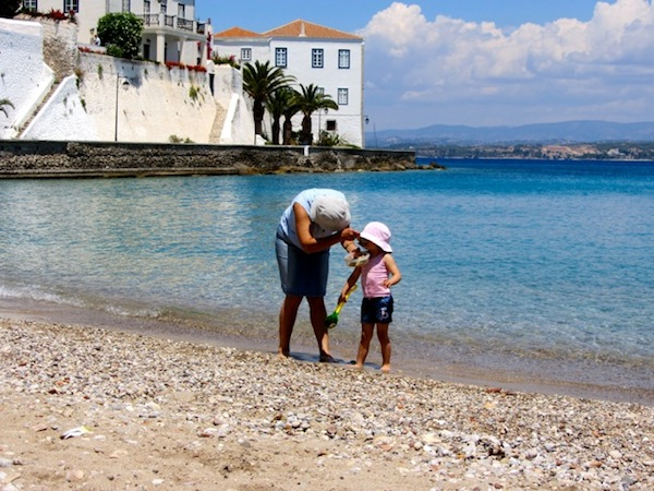 Greek mothers still chase kids with spoons on that Spetses beach.