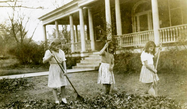 Young girls raking in the foreyard of the Townville house, c. 1950.