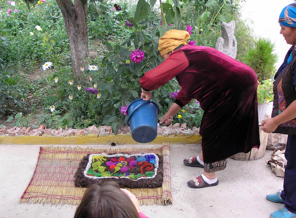 Feltmaker pouring hot water over a design made with dyed wool on a natural beaten wool base.
