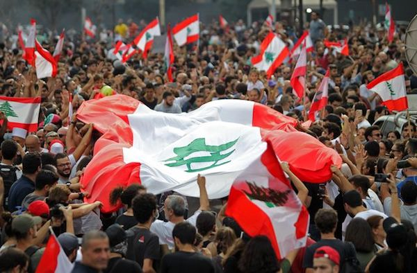 """Lebanese demonstrators wave the national flag during a protest against dire economic conditions in downtown Beirut, Oct. 18, 2019."" (Photo: ""US News & World Report."")"