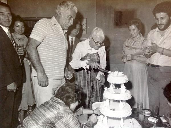 Jacky cutting her birthday cake with fierce determination.